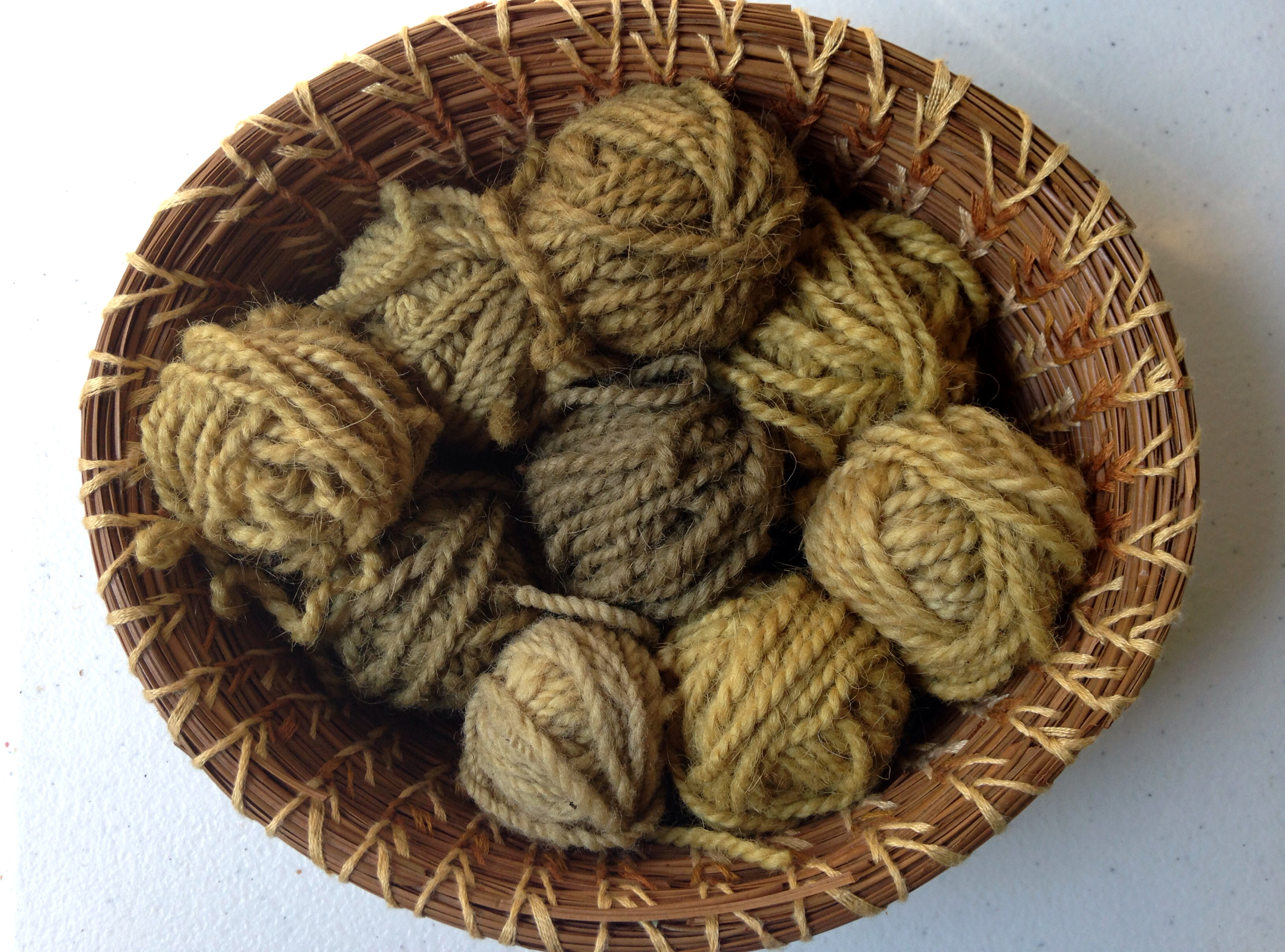 stinging nettle plant dye, natural dye, balls of yarn in a coiled pine needle basket