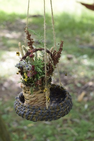 a creative coiled basket with a twined basket planter inside